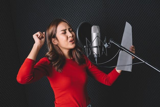 Ładna azjatycka piosenkarka nagrywa piosenki za pomocą mikrofonu studyjnego i popowej osłony mikrofonu z pasją w muzycznym studiu nagrań.