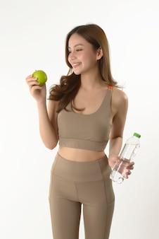 Ładna azjatykcia kobieta z jabłkiem i wodą na bielu