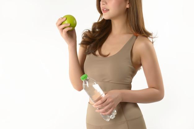 Ładna azjatykcia kobieta z jabłkiem i wodą