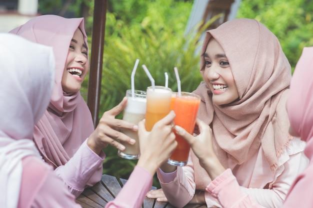 Ładna azjatykcia muzułmańska kobieta ma zabawę w kawiarni wraz z przyjaciółmi