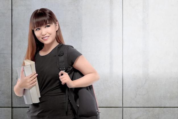 Ładna azjatykcia student collegu kobieta z książką