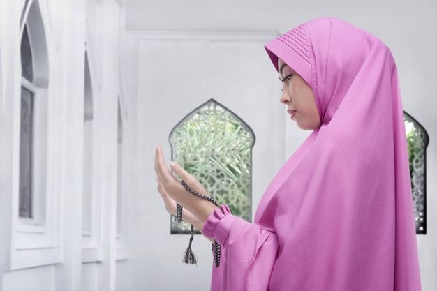 Ładna azjatykcia żeńska muzułmańska dźwiganie ręka i modlenie