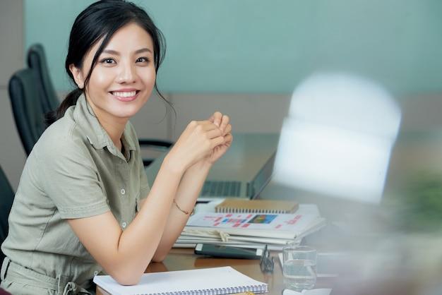 Ładna biznesowa dama pozuje przy jej pracy biurkiem ono uśmiecha się przy kamerą