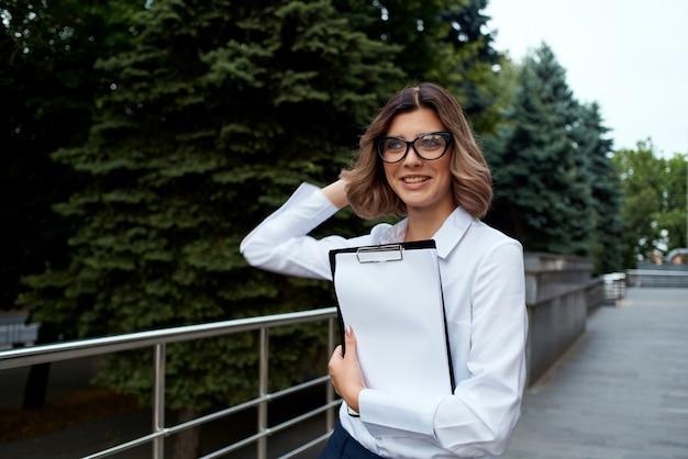 Ładna biznesowa kobieta na zewnątrz z dokumentami pracy. zdjęcie wysokiej jakości