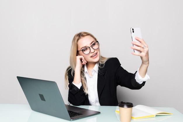 Ładna biznesowa kobieta trzyma jej telefon komórkowego z jedną ręką i robi rozmowie wideo przy biurowym biurkiem w biurze
