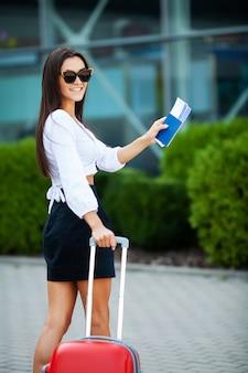 Ładna biznesowa kobieta z czerwoną walizką blisko lotniska