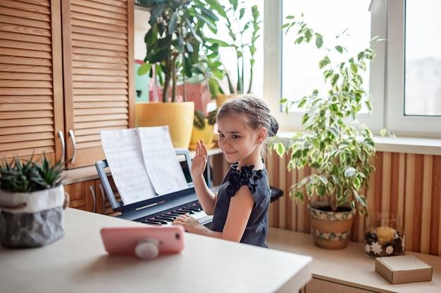 Ładna blogerka grająca na klasycznym pianinie cyfrowym i nagrywająca wideo jak z koncertu online w domu