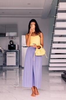 Ładna blogerka modowa ubrana w żółty top i fioletowe spodnie