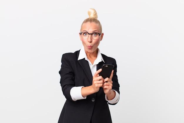 Ładna blond bizneswoman ze smartfonem