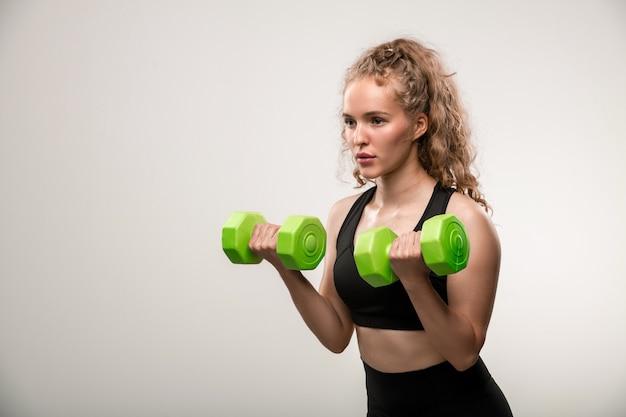 Ładna blond dziewczyna z kręconymi włosami robi ćwiczenia na mięśnie ramion z hantlami podczas treningu