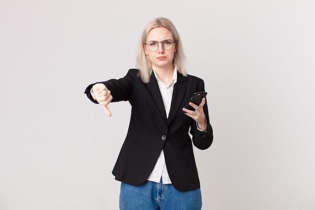 Ładna blond kobieta czuje krzyż, pokazując kciuk w dół i trzymająca telefon komórkowy