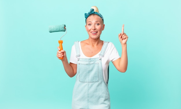 Ładna blond kobieta czuje się jak szczęśliwy i podekscytowany geniusz po zrealizowaniu pomysłu i pomalowaniu ściany
