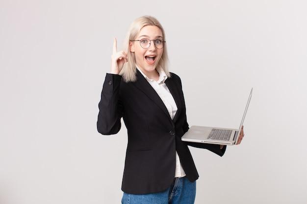Ładna blond kobieta czuje się jak szczęśliwy i podekscytowany geniusz po zrealizowaniu pomysłu i trzymaniu laptopa