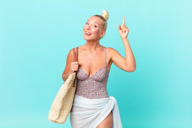 Ładna blond kobieta czuje się jak szczęśliwy i podekscytowany geniusz po zrealizowaniu pomysłu. koncepcja lato