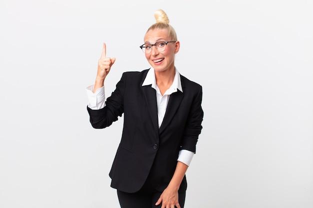 Ładna blond kobieta czuje się jak szczęśliwy i podekscytowany geniusz po zrealizowaniu pomysłu. pomysł na biznes