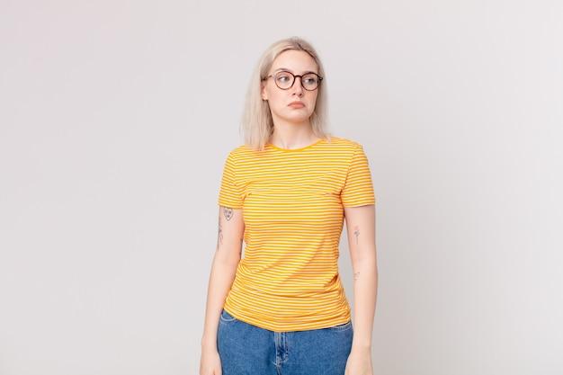 Ładna blond kobieta czuje się smutna, zdenerwowana lub zła i patrzy w bok