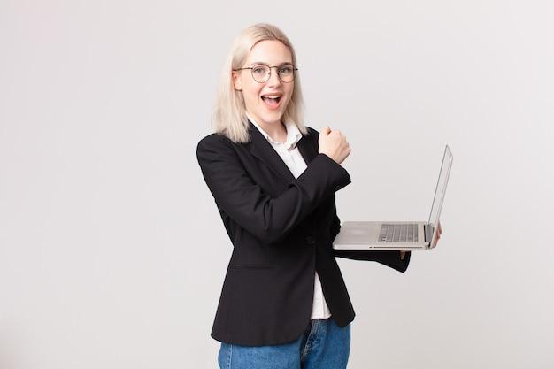 Ładna blond kobieta czuje się szczęśliwa i staje przed wyzwaniem lub świętuje i trzyma laptopa