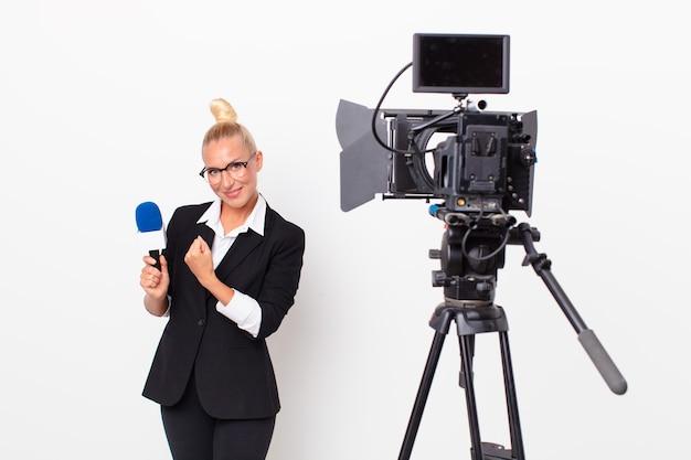 Ładna blond kobieta czuje się szczęśliwa i stoi przed wyzwaniem lub świętuje i trzyma mikrofon. koncepcja prezentera