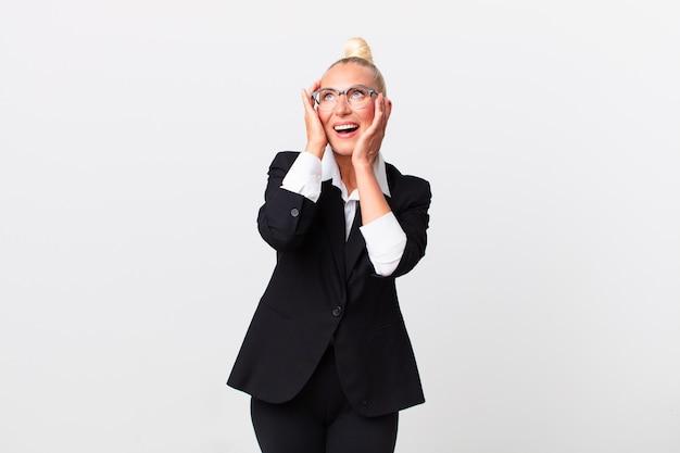 Ładna blond kobieta czuje się szczęśliwa, podekscytowana i zaskoczona. pomysł na biznes