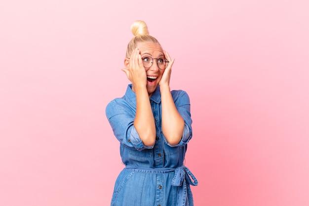 Ładna blond kobieta czuje się szczęśliwa, podekscytowana i zaskoczona