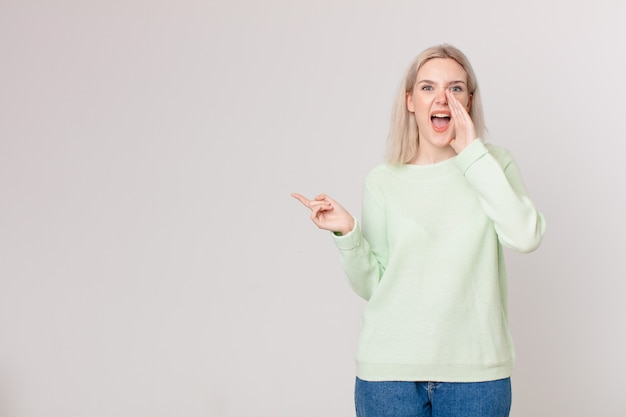 Ładna blond kobieta czuje się szczęśliwa, wydając wielki okrzyk z rękami przy ustach