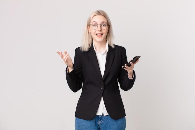 Ładna blond kobieta czuje się szczęśliwa, zaskoczona, gdy zdaje sobie sprawę z rozwiązania lub pomysłu i trzyma telefon komórkowy