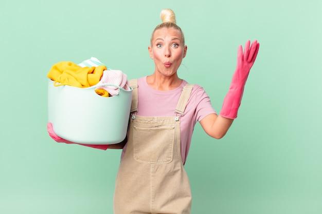 Ładna blond kobieta czuje się wyjątkowo zszokowana i zaskoczona koncepcją prania ubrań