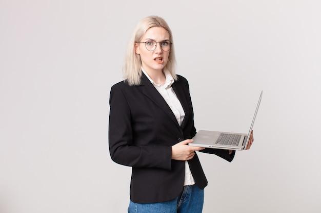 Ładna blond kobieta czuje się zakłopotana i zdezorientowana, trzymając laptopa