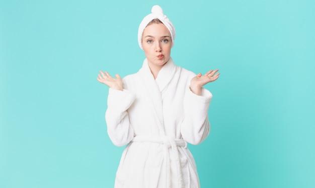 Ładna blond kobieta czuje się zakłopotana i zdezorientowana, wątpi i nosi szlafrok