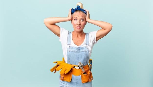 Ładna blond kobieta czuje się zestresowana, niespokojna lub przestraszona, z rękami na głowie i naprawiającą koncepcję domu
