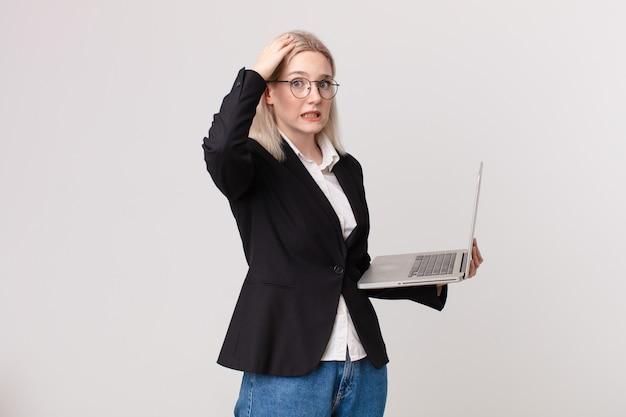 Ładna blond kobieta czuje się zestresowana, niespokojna lub przestraszona, z rękami na głowie i trzymająca laptopa