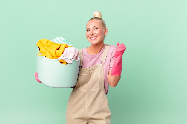 Ładna blond kobieta czuje się zszokowana, śmieje się i świętuje sukces koncepcji prania ubrań