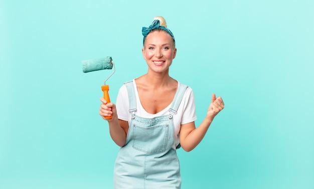 Ładna blond kobieta czuje się zszokowana, śmieje się, świętuje sukces i maluje ścianę