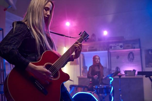 Ładna blond kobieta grająca na gitarze elektrycznej podczas występu na scenie
