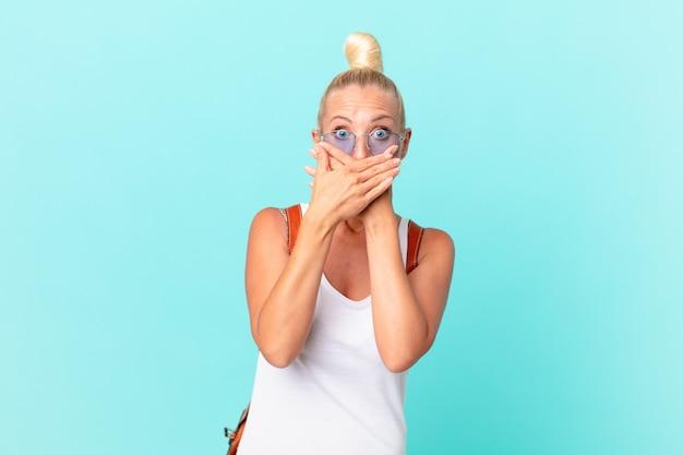 Ładna blond kobieta nakrywa usta rękami z szokiem. koncepcja lato
