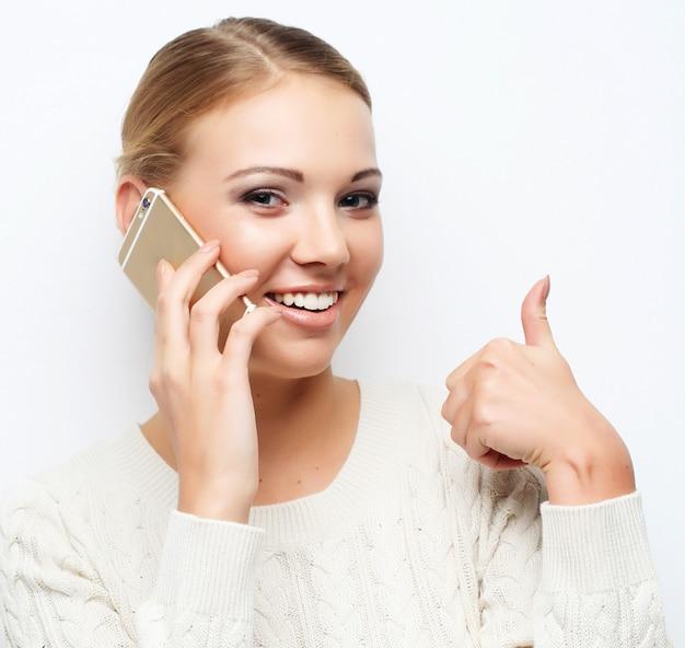 Ładna blond kobieta opowiada na telefonie komórkowym