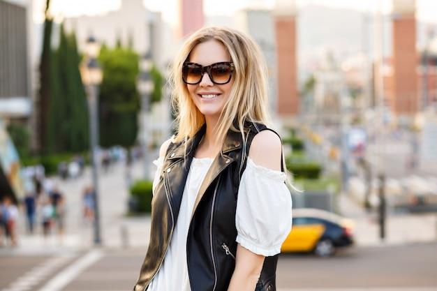 Ładna blond kobieta pozuje przy pięknej europejskiej ulicy, ubrana w strój codzienny i okulary przeciwsłoneczne