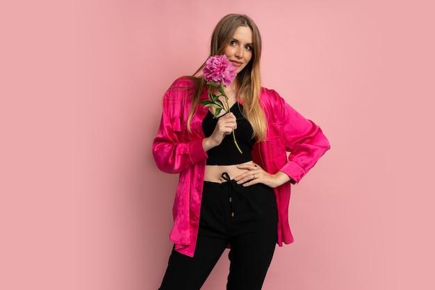 Ładna blond kobieta pozuje z kwiatem piwonii w stylowym letnim stroju na różowej ścianie