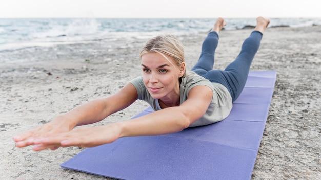 Ładna blond kobieta praktykuje jogę na świeżym powietrzu