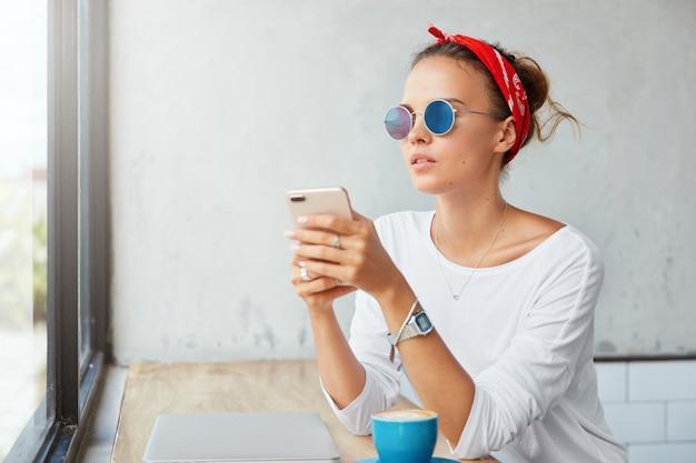 Ładna blond kobieta siedzi w kawiarni