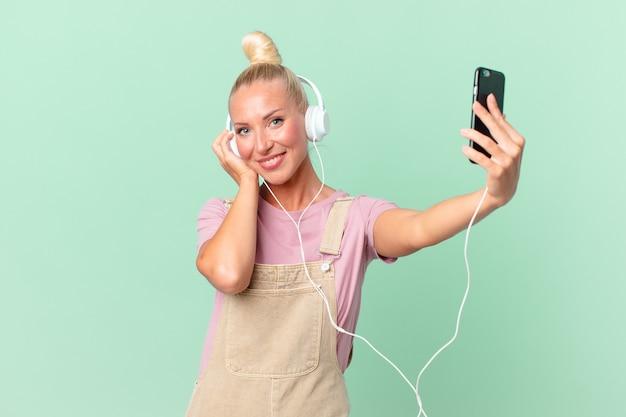 Ładna blond kobieta słucha muzyki przez słuchawki