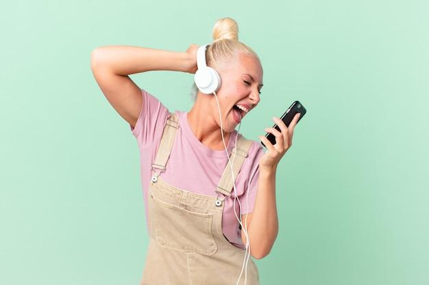 Ładna Blond Kobieta Słucha Muzyki Przez Słuchawki Premium Zdjęcia