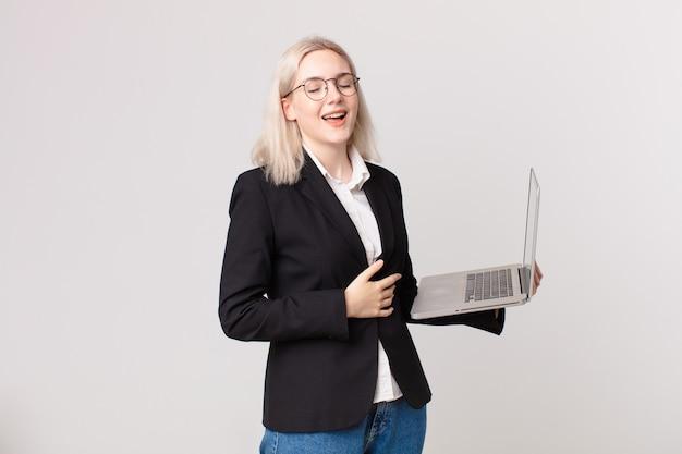 Ładna blond kobieta śmiejąca się głośno z jakiegoś przezabawnego żartu i trzymająca laptopa