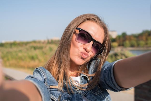 Ładna blond kobieta sprawia, że selfie. pokazuje pocałunek