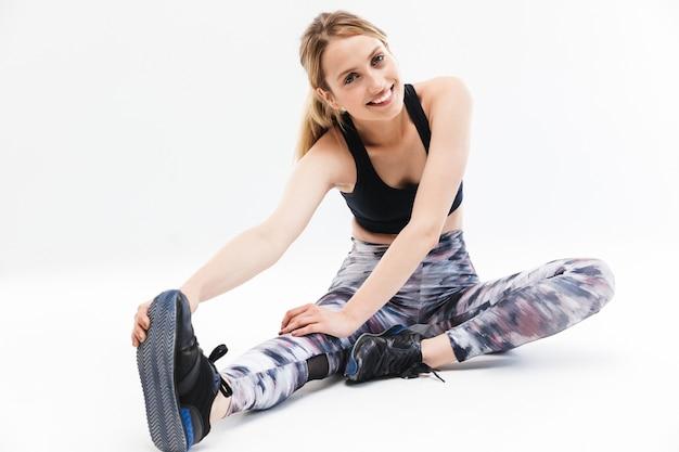 Ładna blond kobieta ubrana w strój sportowy ćwiczący i rozciągający ciało podczas aerobiku na białym tle nad białą ścianą