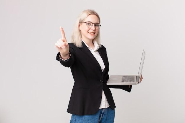 Ładna blond kobieta uśmiecha się dumnie i pewnie robi numer jeden i trzyma laptopa