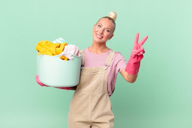 Ładna blond kobieta uśmiecha się i wygląda na szczęśliwą, gestykulując zwycięstwo lub pokój, koncepcja prania ubrań