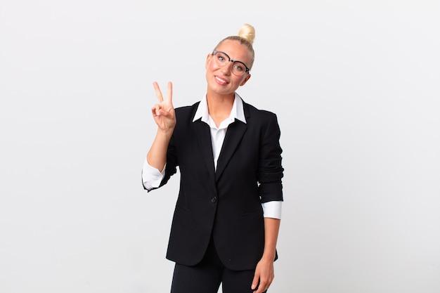 Ładna blond kobieta uśmiecha się i wygląda na szczęśliwą, gestykulując zwycięstwo lub pokój. pomysł na biznes