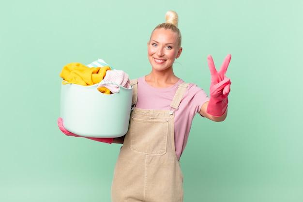 Ładna blond kobieta uśmiecha się i wygląda przyjaźnie, pokazując koncepcję prania ubrań numer dwa