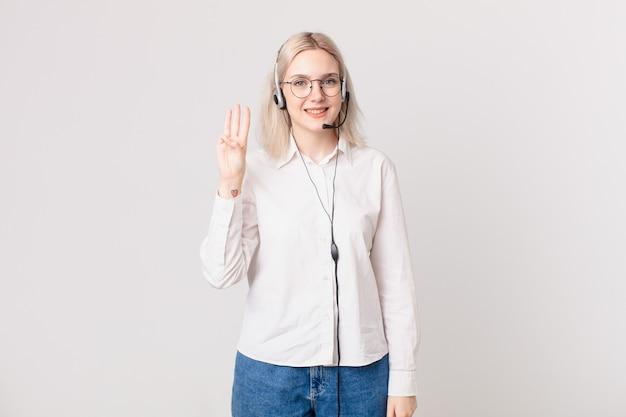 Ładna blond kobieta uśmiecha się i wygląda przyjaźnie, pokazując koncepcję telemarketingu numer trzy three